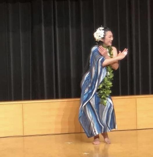 青いフラのドレスを着た女性がイベントでフラダンスを踊っている